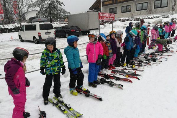 Kinder mit Skiern in einer Reihe