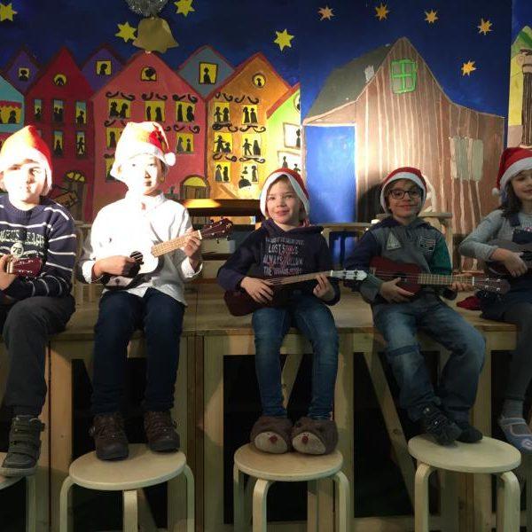 5 Kinder bei der Weihnachtsaufführung am musizieren