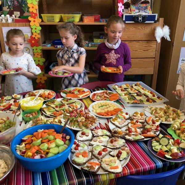 Kinder vor einem üppigen gesunden Frühstücksbuffet