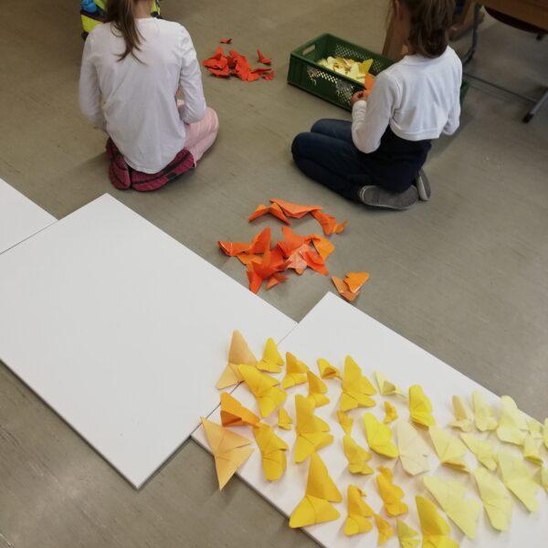 Schülerinnen sortieren Papierschmetterlinge