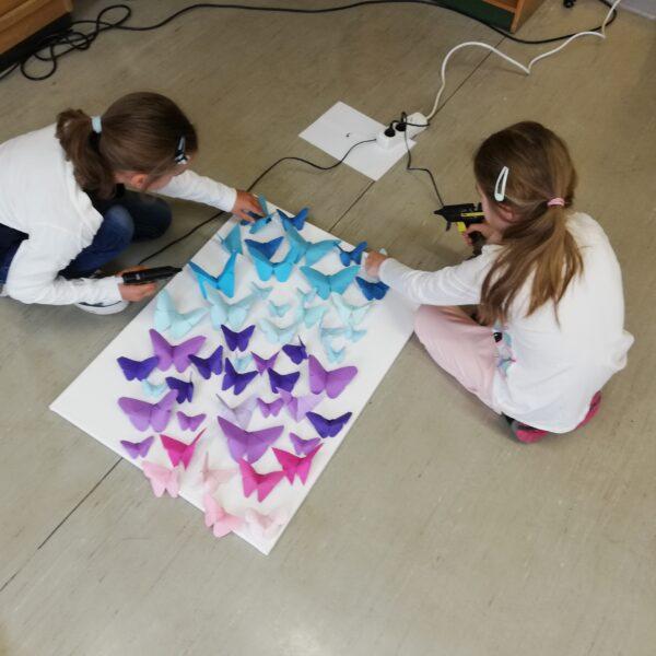Schülerinnen kleben Schmetterlinge