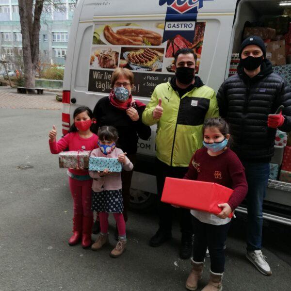 Kinder präsentieren Weihnachtspäckchen vor Transporter